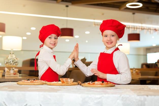 Twee mooie koksmeisjes in witte overhemden en rode schorten in het restaurant maken pizza