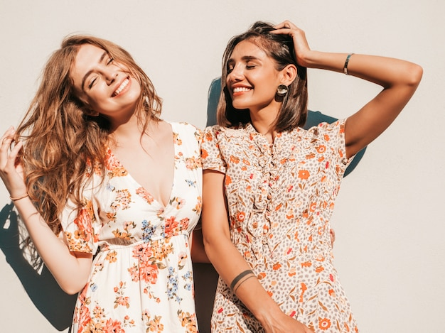 Twee mooie lachende meisjes in trendy zomer sundress poseren op straat