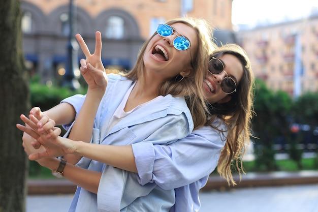 Twee mooie lachende meisjes in trendy zomerkleren poseren op straat achtergrond. modellen hebben plezier en knuffelen.