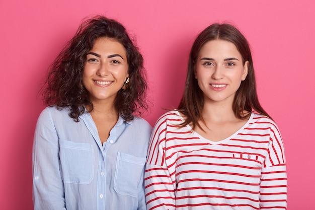 Twee mooie lachende meisjes met donker haar poseren tegen roze ruimte