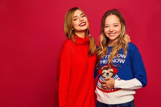 Twee mooie lachende prachtige meisjes camera kijken. vrouwen staan in stijlvolle winter warme truien op rode achtergrond. kerstmis, kerstmis, concept