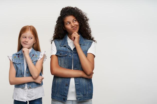 Twee mooie langharige jongedames die hun hoofd op opgeheven handen leunen en hun lippen verdraaiden, bedachtzaam opzij kijkend terwijl ze op wit stonden