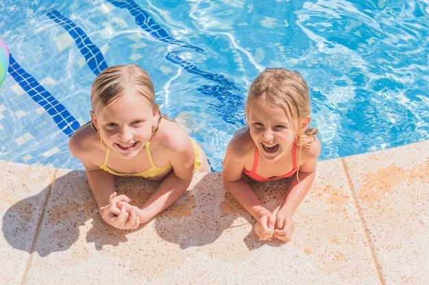 Twee mooie meisjes bij zwembad in de zomer