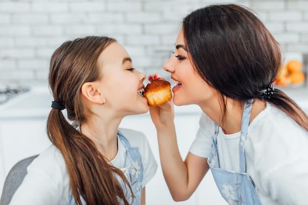 Twee mooie meisjes die cupcakes proeven in de keuken