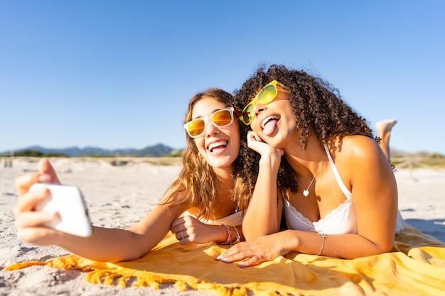 Twee mooie meisjes die in de zomer op het strand liggen en plezier maken met het maken van gezichten met hun tong uit