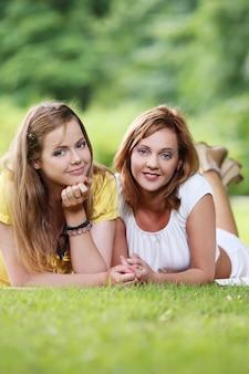 Twee mooie meisjes die in het park hangen