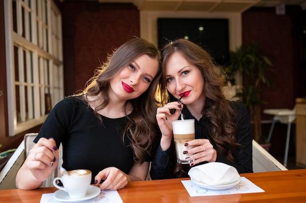 Twee mooie meisjes die koffie drinken