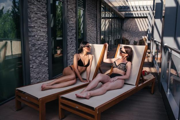 Twee mooie meisjes die op de ligstoelen liggen en ontspannen.