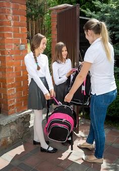 Twee mooie meisjes die 's ochtends naar school gaan en afscheid nemen van hun moeder