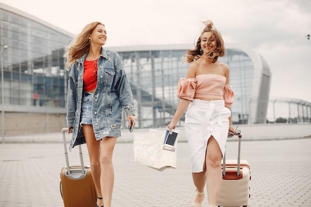 Twee mooie meisjes die zich bij de luchthaven bevinden