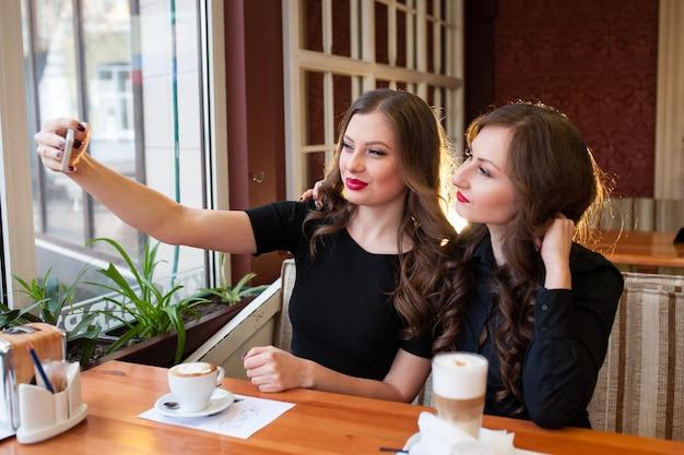 Twee mooie meisjes doen selfi en drinken koffie