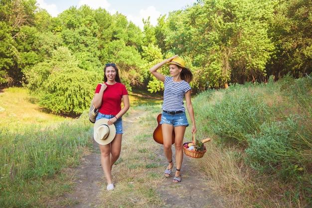 Twee mooie meisjes gaan op een picknick op het pad in het bos