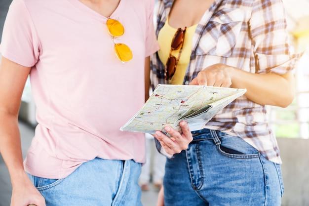 Twee mooie meisjes gaan zitten om de kaart te zien.