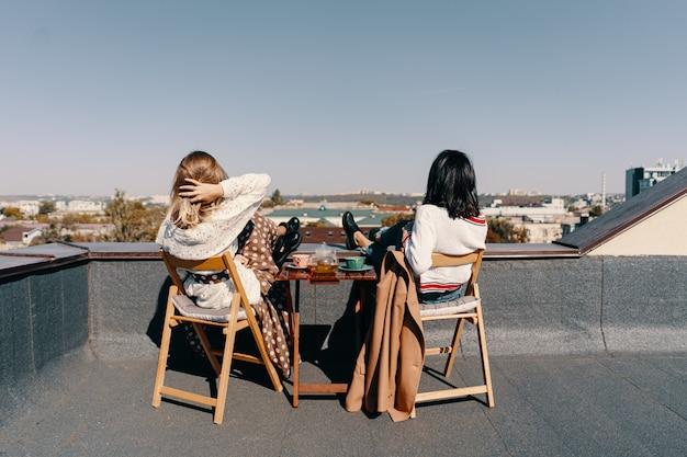 Twee mooie meisjes genieten van een theekransje op het dak met uitzicht over de stad