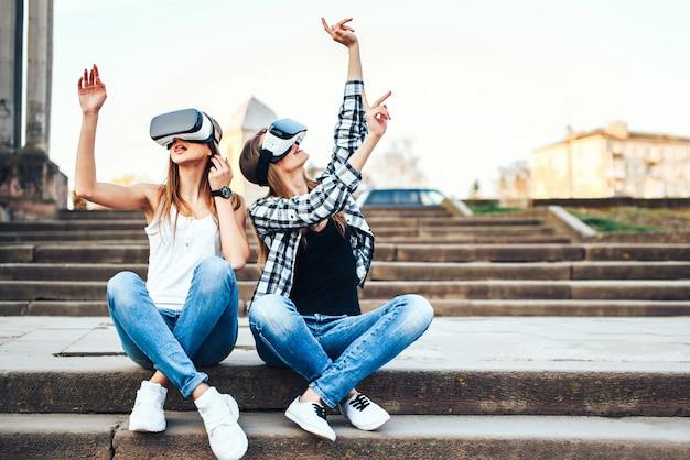 Twee mooie meisjes genieten van virtual reality-bril buiten