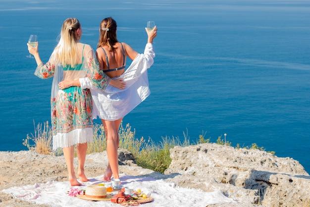 Twee mooie meisjes in badpakken op de achtergrond van de zee