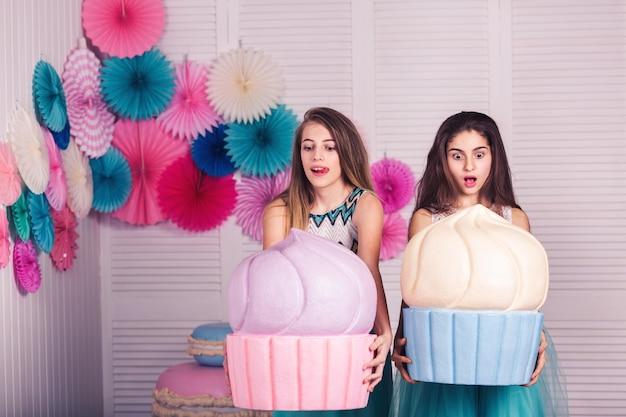 Twee mooie meisjes in blauwe jurken houden enorme taarten in hun handen. emoties: shock, wauw, ongelooflijk, hongerig, wil eten.