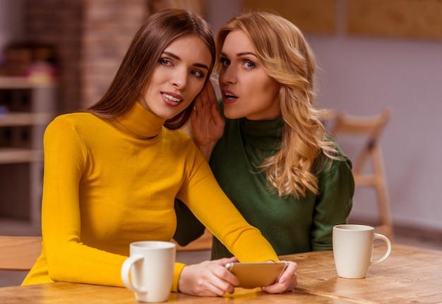Twee mooie meisjes in casual kleding met behulp van smartphone.