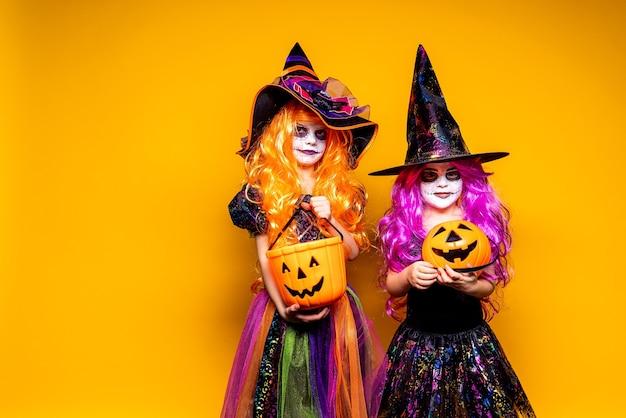 Twee mooie meisjes in een heksenkostuum en hoeden op een gele achtergrond die en gezichten doen schrikken.