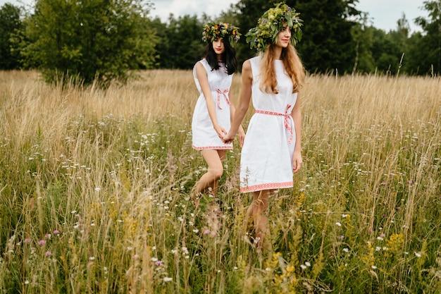Twee mooie meisjes in etnische jurken lopen in veld.
