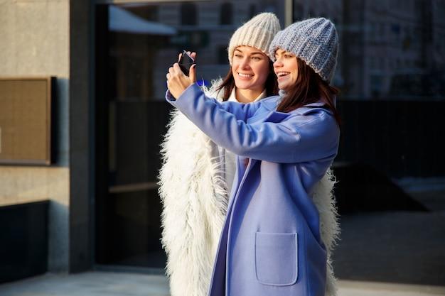 Twee mooie meisjes in kappen van wol die selfie gebruikend een smartphone in openlucht in de winter nemen