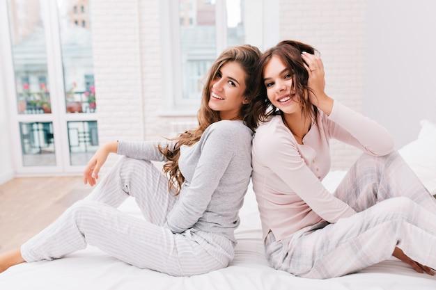 Twee mooie meisjes in pyjama's zitten rijtjes op wit bed in lichte kamer. ze glimlachen.