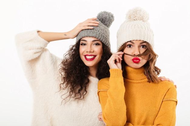 Twee mooie meisjes in sweaters en hoeden die samen over witte muur stellen