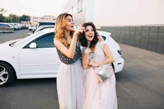 Twee mooie meisjes in tule rokken die plezier hebben op de parkeerplaats. ze zagen er ver weg verrast en opgewonden uit.