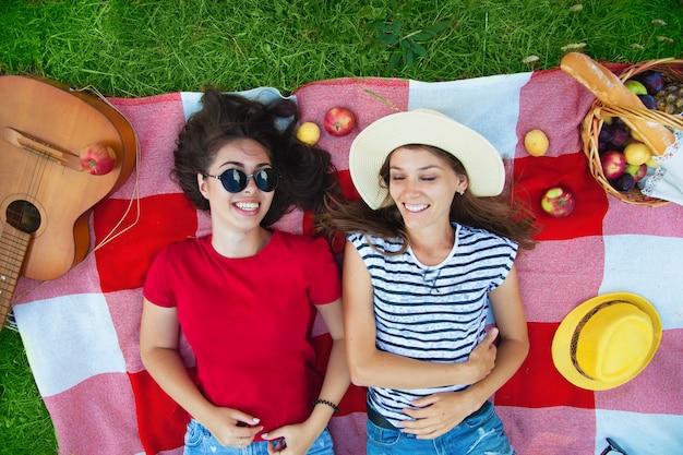 Twee mooie meisjes in zonnebril plezier op een picknick in het bos bovenaanzicht