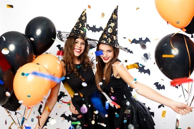 Twee mooie meisjes in zwarte jurken en heksenhoeden hebben plezier met zwarte en oranje ballonnen en confetti. halloween feest .