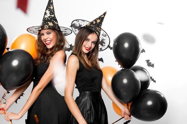 Twee mooie meisjes in zwarte jurken en heksenhoeden hebben plezier met zwarte en oranje ballonnen. halloween.