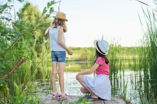 Twee mooie meisjes kinderen zitten op houten pier van het meer in riet, spelen met water, praten, achteraanzicht. zomervakantie, natuur, gelukkige jeugd, vriendschap, landelijke stijl.