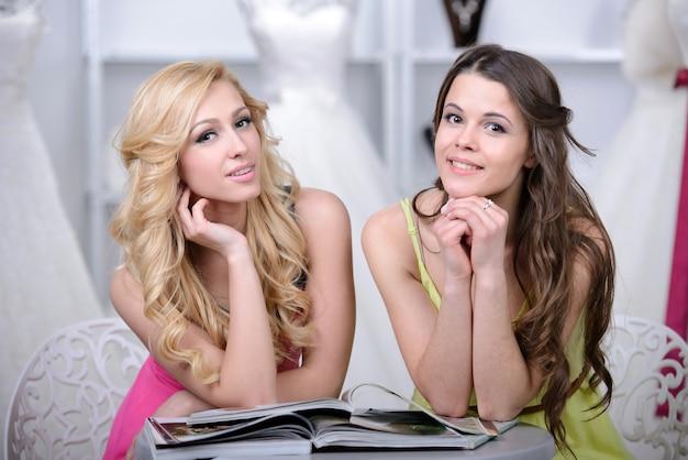 Twee mooie meisjes leunden op ellebogen en poseren.