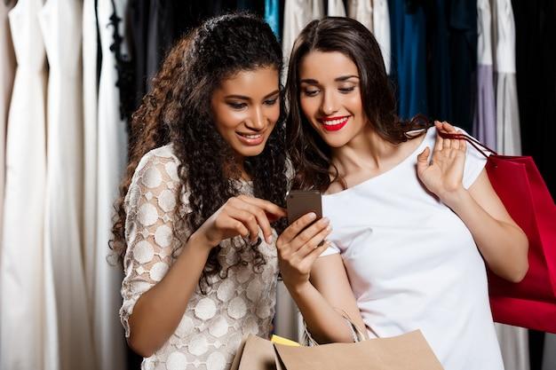 Twee mooie meisjes maken winkelen, kijken naar telefoon in winkelcentrum.