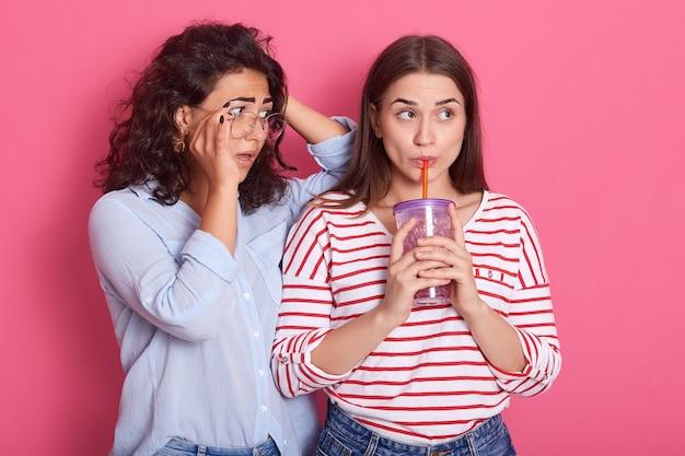 Twee mooie meisjes met donker haar poseren tegen roze ruimte