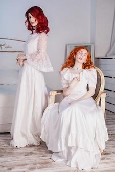 Twee mooie meisjes met rood haar in een prachtige witte victoriaanse trouwjurken. vrouwelijke stijl. het kwetsbare meisje. dunne taille. een vrouw zit op een stoel. conceptuele fotografie