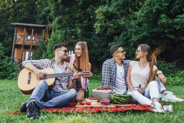 Twee mooie meisjes met twee jongens zitten in een park op een deken met gitaar, ze hebben picknick en luisteren melodie van gitaar