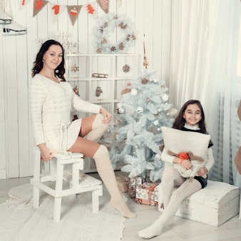 Twee mooie meisjes, moeder en dochter die in een kerstmis verfraaide ruimte situeren.