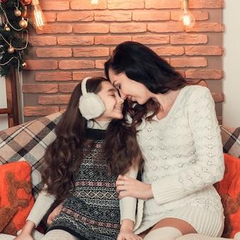 Twee mooie meisjes, moeder en dochter die op bank in kerstmis verfraaide ruimte situeren.
