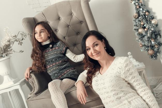 Twee mooie meisjes, moeder en dochter die op een vloer in kerstmis verfraaide ruimte situeren.