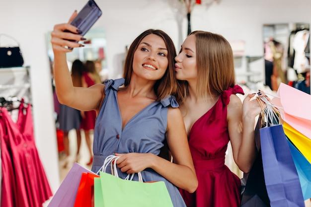 Twee mooie meisjes nemen selfies na het winkelen in de winkel