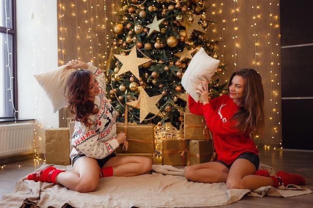 Twee mooie meisjes op oudejaarsavond. jonge vrouw beste vrienden die kerstmis in huis vieren. plezier vriendschap eindigt nooit concept. prachtige gouden kerstversiering op een hoge kerstboom