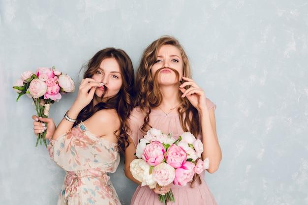 Twee mooie meisjes staan in een studio, houden boeketten bloemen vast en spelen gek.