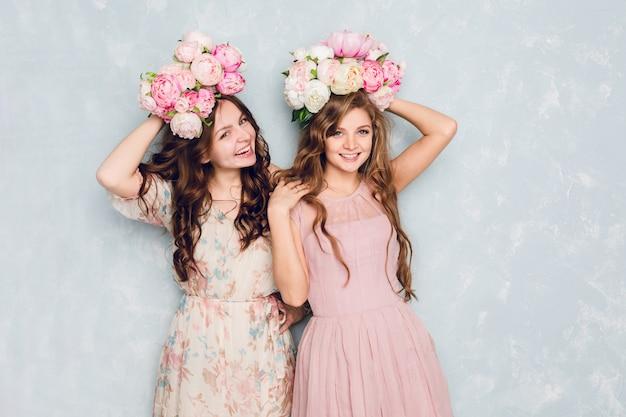 Twee mooie meisjes staan in een studio, spelen gek en hebben bloemencirkels op hun hoofd.