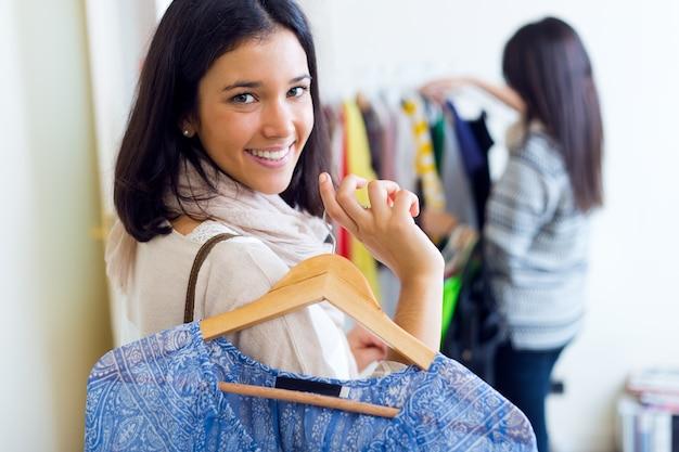 Twee mooie meisjes winkelen in een kledingwinkel.