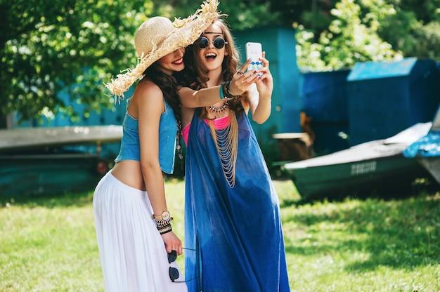 Twee mooie meisjeshippie om selfie dichtbij oude boot te maken