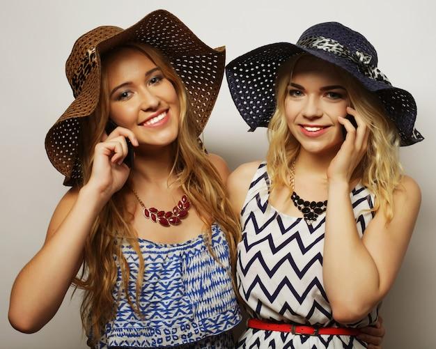 Twee mooie meisjesvrienden met mobiel, studioschot