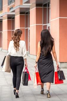 Twee mooie modieuze jonge vrouwen lopen in het winkelcentrum met tassen, achteraanzicht