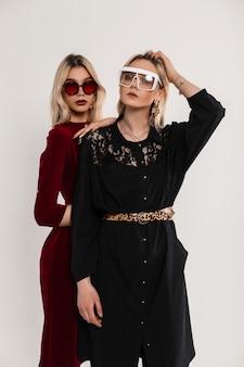 Twee mooie modieuze tweelingzussen met zonnebril in elegante trendy vintage jurk in de buurt van grijze muur