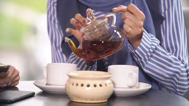 Twee mooie moslimmeisjes in cafe.